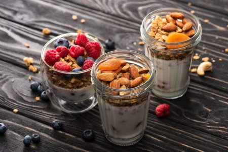delicious granola with berries, dried apricots, nuts and yogurt in glass cups on wooden surface