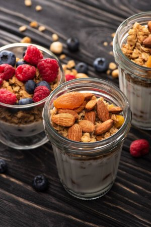 closeup of delicious granola with berries, dried apricots, nuts and yogurt in glass cups on wooden surface