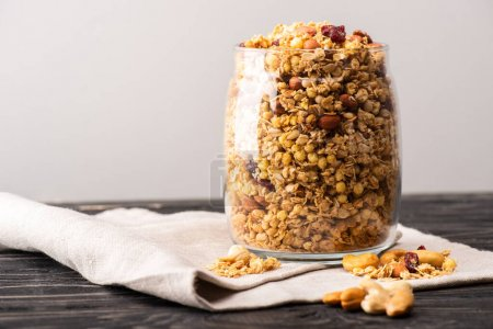 delicious granola in glass gar on napkin isolated on grey