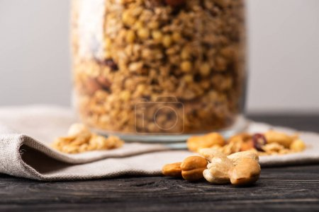 Photo for Blurred delicious granola in glass gar on napkin and nuts - Royalty Free Image