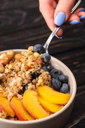 Photo for Cropped view of woman eating delicious granola with nuts, peach, blueberry - Royalty Free Image