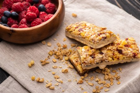 delicious muesli bars on napkin with blurred berries
