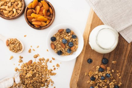 top view of delicious granola with yogurt, nuts, blueberry and dried apricots isolated on white