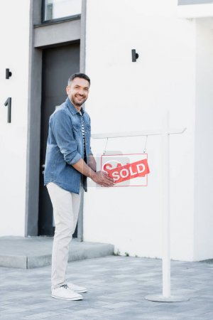 Photo for Full length of smiling man holding sign with sold lettering near house - Royalty Free Image