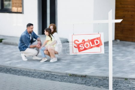 Sign with sold lettering with blurred family squatting near house on background