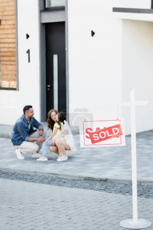 Sign with sold lettering with blurred happy family near house on background