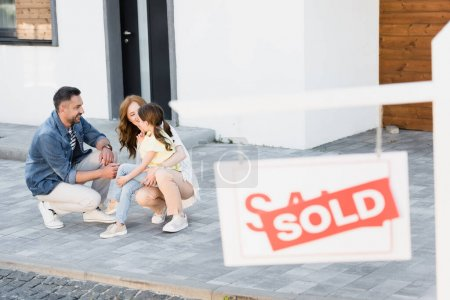 Happy family squatting near house with blurred sign with sold lettering on foreground
