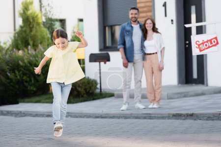 Photo for Smiling girl running with blurred father and mother hugging on background near house - Royalty Free Image
