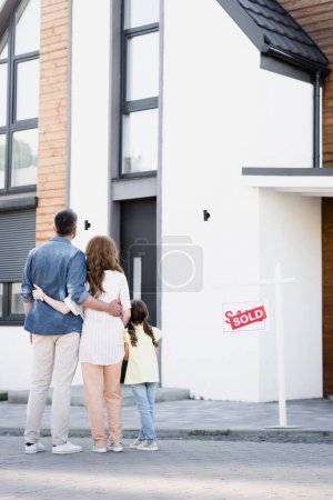 Full length of daughter standing near father and mother hugging near house and sign with sold lettering