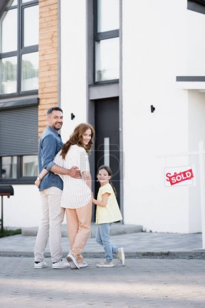 Photo for Full length of smiling family with daughter looking at camera while standing near house and sign with sold lettering - Royalty Free Image