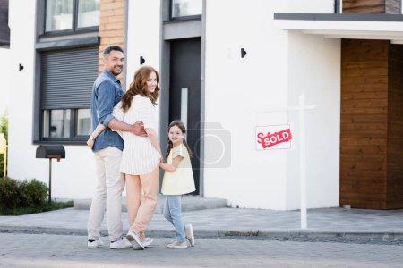 Longitud completa de la familia feliz con la hija mirando a la cámara mientras está de pie cerca de la casa y firmar con letras vendidas