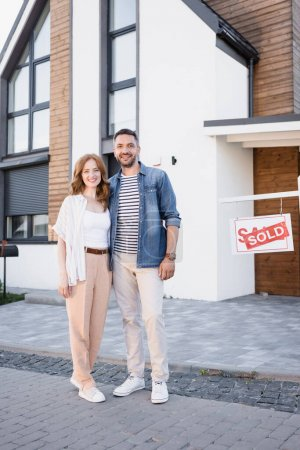 Full length of smiling couple hugging and looking at camera near sign with sold lettering and house