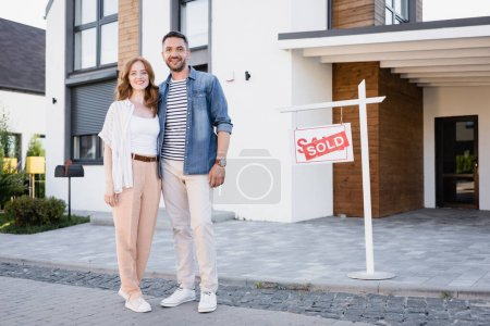 Photo for Full length of happy couple looking at camera and hugging while standing near sign with sold lettering and house - Royalty Free Image