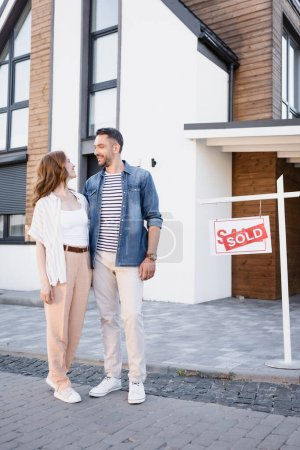 Photo for Full length of smiling couple looking at each other while hugging near house and sign with sold lettering - Royalty Free Image
