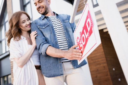 Photo for Low angle view of smiling couple holding sign with sold lettering near house - Royalty Free Image