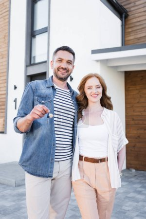 Mujer feliz abrazando hombre con llave y mirando a la cámara cerca de casa