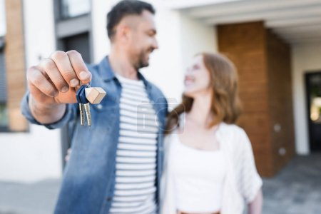 Photo for Keys and fob in hands of happy husband looking and hugging wife near house on blurred background - Royalty Free Image