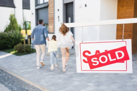 Photo for Back view of family going to house near sign with sold lettering on blurred background - Royalty Free Image