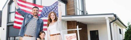 Photo pour Couple heureux avec fille regardant la caméra tout en tenant drapeau américain près signe avec lettrage vendu et maison, bannière - image libre de droit