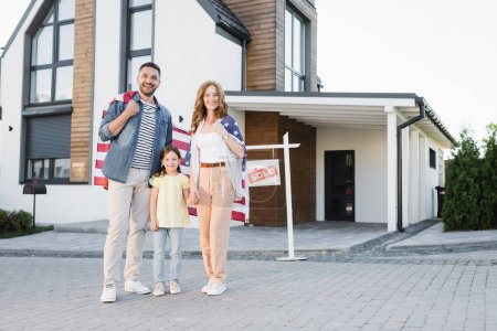 Photo for Full length of happy daughter with mom and dad holding american flag while standing together and looking at camera near house - Royalty Free Image