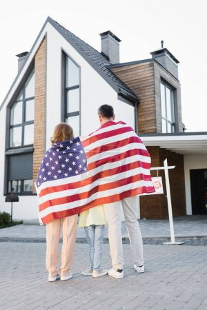 Back view of daughter with mom and dad covered with american flag while standing together near house