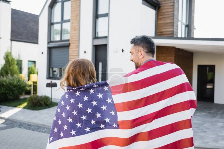 Back view of couple covered with american flag near house on blurred background