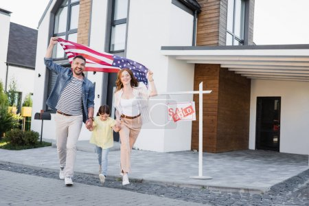 Daughter with happy mom and dad holding american flag going forward near sign with sold lettering and house