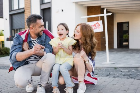 Photo for Excited daughter with open mouth sitting near mother and father showing keys with blurred house on background - Royalty Free Image