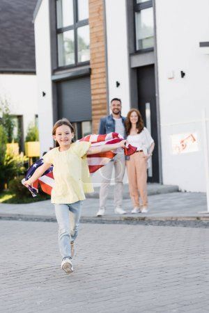 Photo for Full length of happy girl with american flag running forward while looking at camera with blurred parents hugging on background - Royalty Free Image