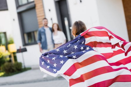 Photo for Back view of daughter holding american flag with blurred parents on background - Royalty Free Image