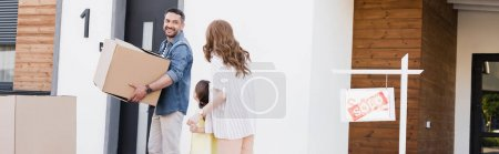 Photo for Smiling husband with carton box looking at wife holding hands with daughter near house and sign with sold lettering, banner - Royalty Free Image