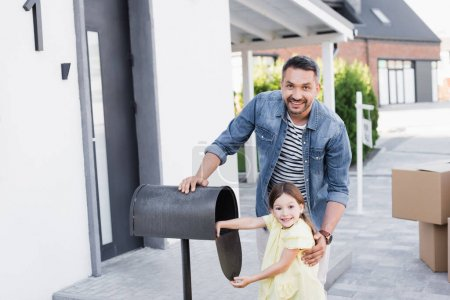Photo for Cheerful father hugging daughter near empty mailbox while looking at camera near house on blurred background - Royalty Free Image