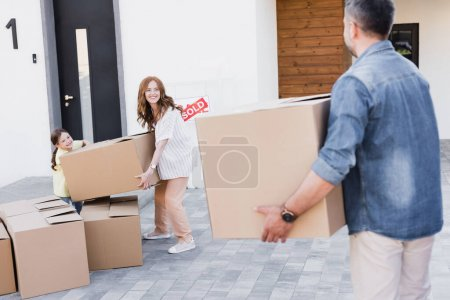 Happy woman and girl holding package while looking at blurred man with carton box on foreground