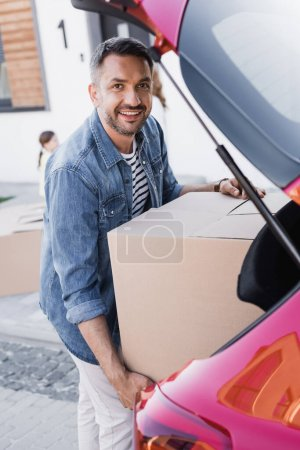 Happy man looking at camera while taking carton box from car trunk on blurred background
