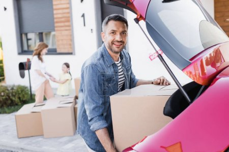 Photo for Smiling man looking at camera while taking carton box from car trunk with blurred woman and girl on background - Royalty Free Image