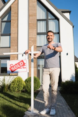 Full length of smiling man showing key while standing near sign with sold lettering with modern house on background