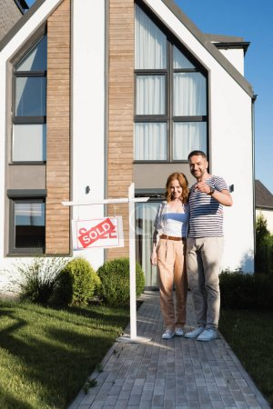 Full length of happy couple with key hugging and looking at camera while standing near modern house and sign with sold lettering