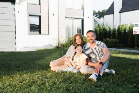 Photo for Happy family looking at camera while sitting on lawn near modern house - Royalty Free Image
