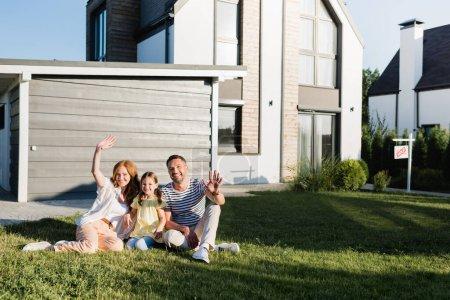 Padres felices con las manos agitadas y la hija sentada en el césped y mirando a la cámara cerca de la casa