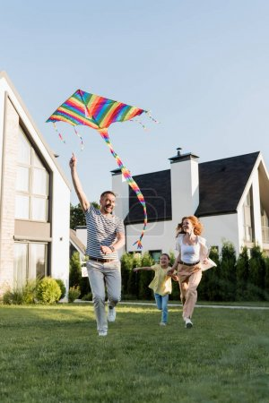 Photo for Full length of happy mother and daughter running near father flying kite on lawn near houses - Royalty Free Image