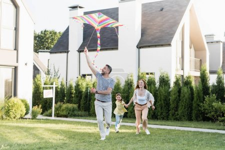 Photo for Full length of happy man flying kite near woman and girl on lawn near houses - Royalty Free Image
