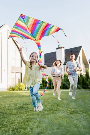 Photo for Happy daughter looking at camera while flying kite with blurred parents on background - Royalty Free Image