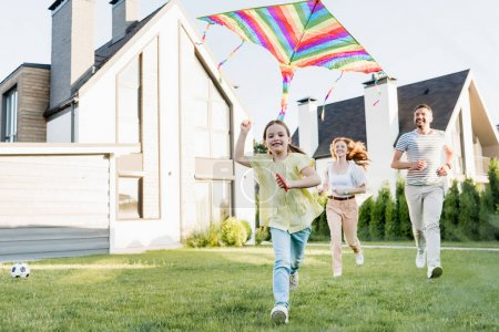 Photo for Happy daughter looking at camera while flying kite with parents running on background near house - Royalty Free Image