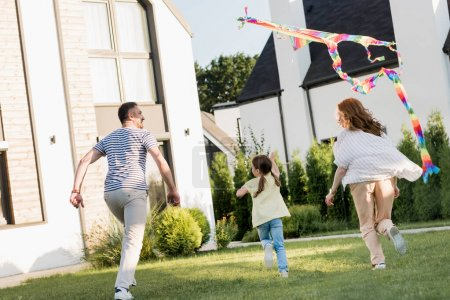 Photo for Back view of family running while flying kite on lawn near home - Royalty Free Image