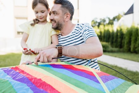 Photo for Smiling father looking at daughter while assembling kite on blurred background - Royalty Free Image