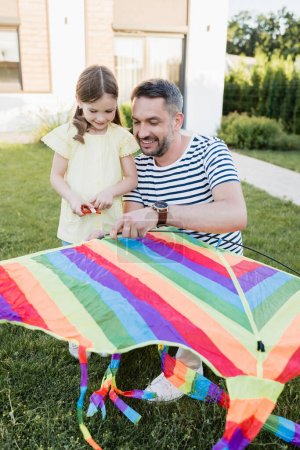 Full length of smiling daughter standing near father assembling kite on lawn with blurred house on background
