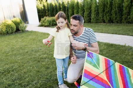 Daughter with kite string holder standing with father squatting near on lawn on blurred background