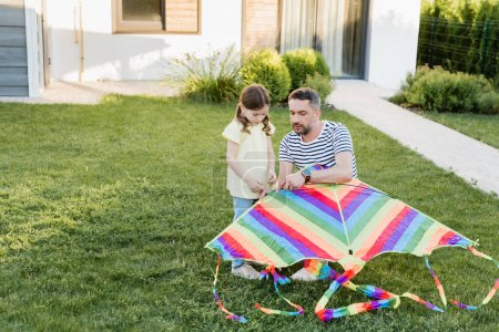 Photo for Full length of daughter standing near father assembling kite on lawn with house on background - Royalty Free Image