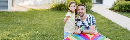 Photo for Happy daughter and father with kite looking at camera on lawn, banner - Royalty Free Image