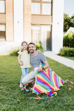 Photo for Happy father with kite hugging daughter and looking at camera on lawn with house on background - Royalty Free Image